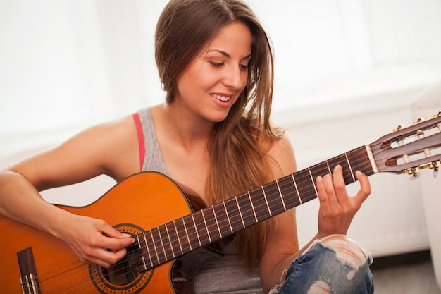 Junge schöne frau, die gitarre spielt