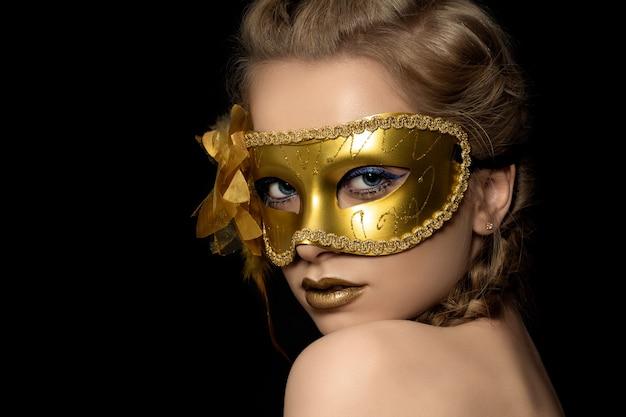 Junge schöne frau, die goldene parteimaske trägt