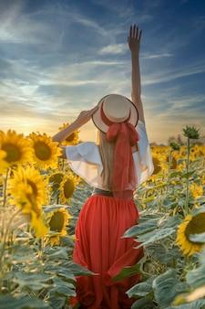 Junge schöne frau, die hände oben in einem sonnenblumenfeld steht
