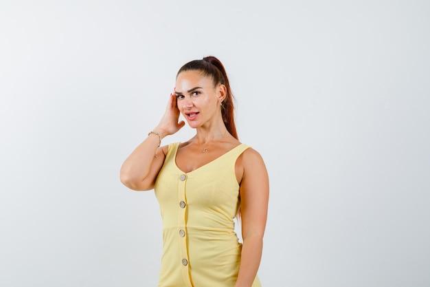 Junge schöne frau, die hand auf kopf hält, während sie im kleid posiert und freudig schaut. vorderansicht.