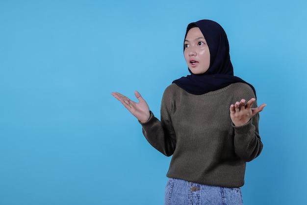 Junge schöne frau, die hilflose geste im t-shirt zeigt, hijab trägt und verwirrt aussieht
