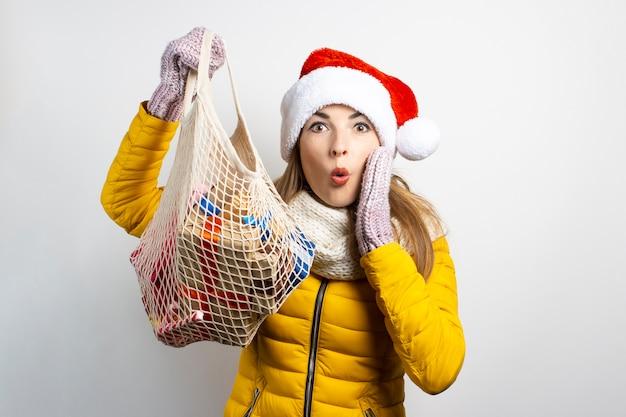 Junge schöne frau, die hut des weihnachtsmannes mit den einkaufstaschen lokalisiert trägt
