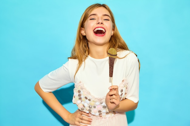 Junge schöne frau, die ihr bestes lied mit gefälschtem mikrofon der stützen singt. modische frau in der zufälligen sommerkleidung. lustiges modell lokalisiert auf blauer wand