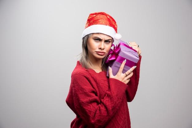 Junge schöne frau, die ihr geschenk auf grauem hintergrund umarmt.