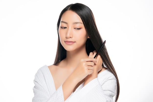 Junge schöne frau, die ihr haar auf weißem hintergrund kämmt.