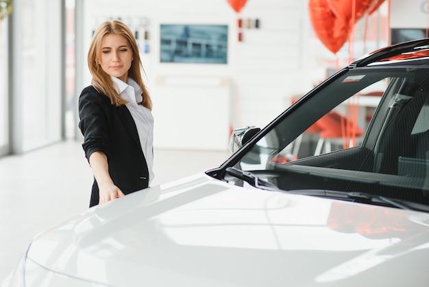 Junge schöne frau, die ihre liebe zu einem auto in einem autohaus zeigt