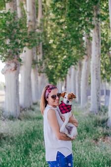 Junge schöne frau, die ihren netten kleinen hund auf schulter anhält. draußen. liebe für tierkonzept und -lebensstil draußen