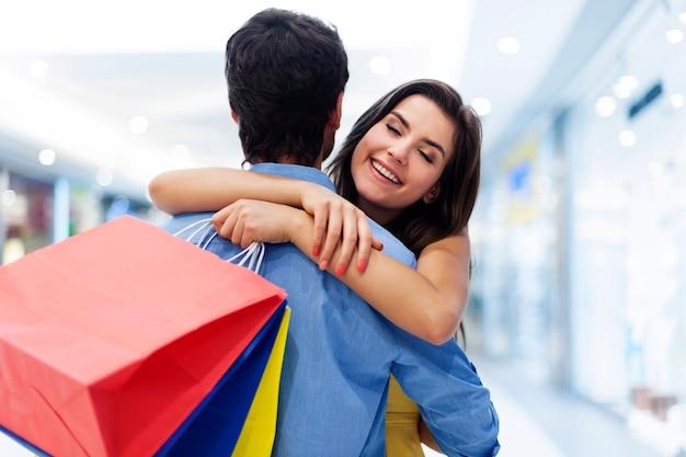 Junge schöne frau, die im einkaufszentrum begrüßt