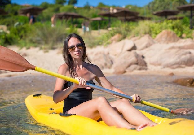 Junge schöne frau, die im freien blauen meer kayak fährt