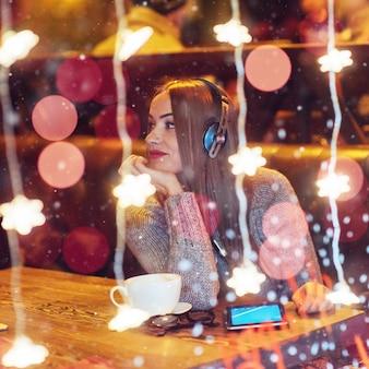 Junge schöne frau, die im kaffee, trinkender kaffee sitzt. vorbildliches hören von musik. weihnachten, guten rutsch ins neue jahr, valentinstag, winterferien
