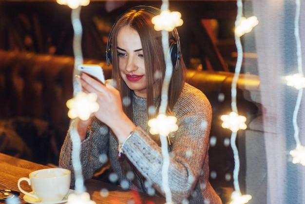 Junge schöne frau, die im kaffee, trinkender kaffee sitzt. vorbildliches hören von musik. weihnachten, neujahr, valentinstag, winterferien