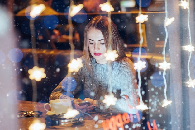 Junge schöne frau, die im kaffee, trinkender kaffee sitzt. weihnachten, neujahr, valentinstag, winterferien