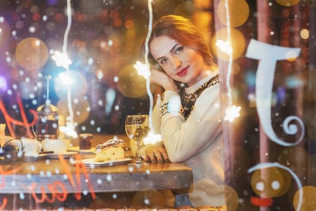 Junge schöne frau, die im kaffee, trinkender wein sitzt. weihnachten, neujahr, valentinstag, winterferien