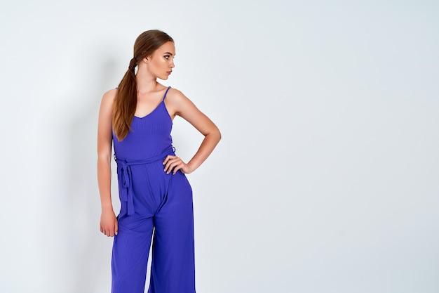 Junge schöne frau, die im neuen lässigen blauen modekostümkleid mit dem vollen körper der hose auf weißem hintergrund aufwirft