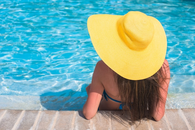 Junge schöne frau, die im swimmingpool sich entspannt