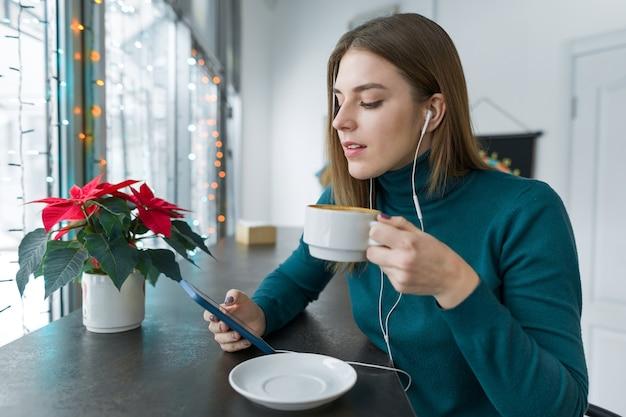 Junge schöne frau, die in der pause im café mit tasse heißem getränk in der herbstwintersaison ruht