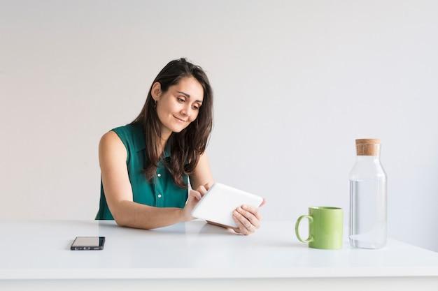 Junge schöne frau, die in einem modernen büro arbeitet. sie benutzt tablet. handy auf dem tisch, wasserkrug und eine grüne tasse kaffee. sie lächelt. modernes bürokonzept