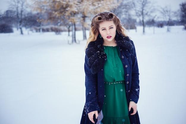 Junge schöne frau, die in einem park geht und frische winterluft atmet und sich wunderbar fühlt. modell plus größe