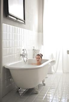 Junge schöne frau, die in einer badewanne liegt und sich ausruht