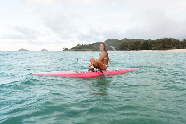 Junge schöne frau, die in hawaii surft