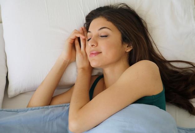 Junge schöne frau, die in ihrem bett schläft und sich am morgen entspannt