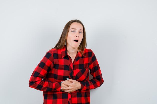 Junge schöne frau, die in lässigem hemd unter magenschmerzen leidet und schmerzhaft aussieht, vorderansicht.