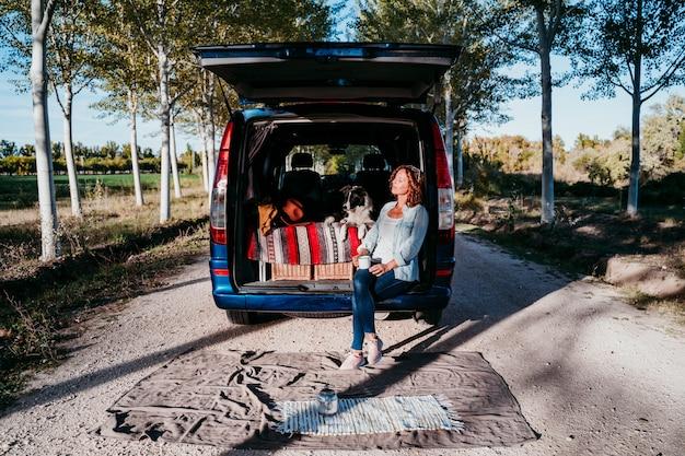 Junge schöne frau, die kaffee- oder teecamping im freien mit einem van und ihren zwei hunden trinkt. reisekonzept