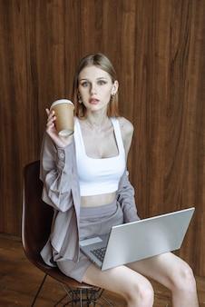 Junge schöne frau, die kaffee trinkt und an laptop-porträt arbeitet