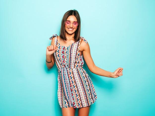 Junge schöne frau, die kamera betrachtet. trendy mädchen im lässigen sommerkleid und in der runden sonnenbrille. positive frau zeigt gesichtsgefühle. lustiges modell lokalisiert auf blau