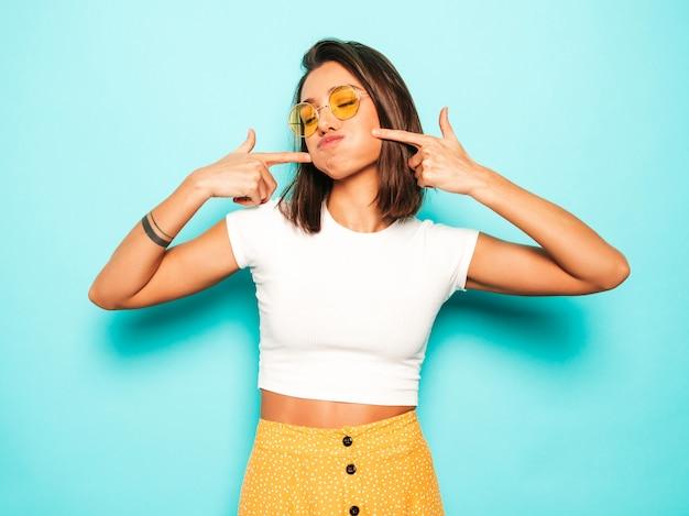 Junge schöne frau, die kamera betrachtet. trendy mädchen im lässigen weißen sommer-t-shirt und im gelben rock in der runden sonnenbrille. positive frau zeigt gesichtsgefühle. lustiges modell, das ihre wangen bläst.
