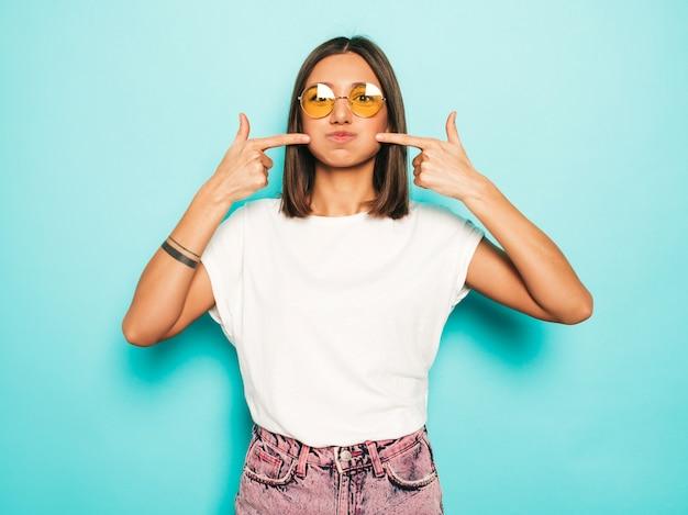 Junge schöne frau, die kamera betrachtet. trendy mädchen im lässigen weißen sommer-t-shirt und in den jeansshorts in der runden sonnenbrille. positive frau zeigt gesichtsgefühle. lustiges modell, das ihre wangen bläst.