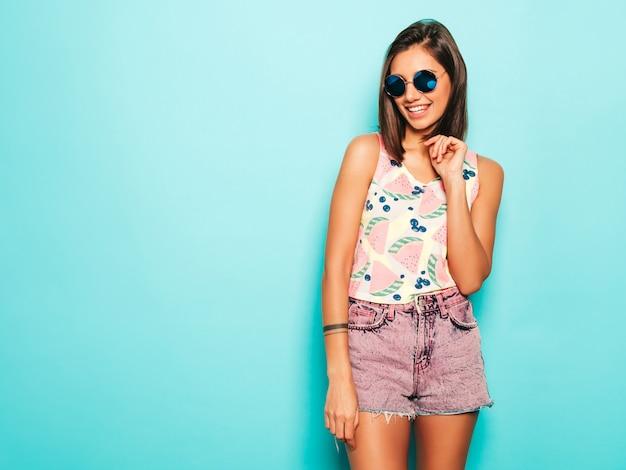Junge schöne frau, die kamera betrachtet. trendy mädchen im lässigen weißen sommer-t-shirt und in den jeansshorts in der runden sonnenbrille. positive frau zeigt gesichtsgefühle. lustiges modell lokalisiert auf blau