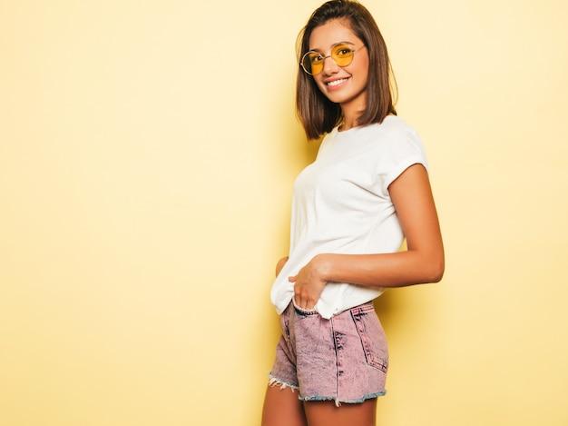 Junge schöne frau, die kamera betrachtet. trendy mädchen im lässigen weißen sommer-t-shirt und in den jeansshorts in der runden sonnenbrille. positive frau zeigt gesichtsgefühle. lustiges modell lokalisiert auf gelb