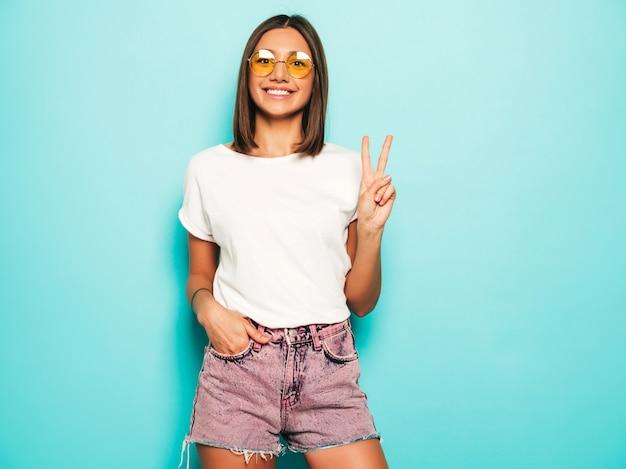Junge schöne frau, die kamera betrachtet. trendy mädchen im lässigen weißen sommer-t-shirt und in den jeansshorts in der runden sonnenbrille. positive frau zeigt gesichtsgefühle. modell isoliert auf blau zeigt friedenszeichen