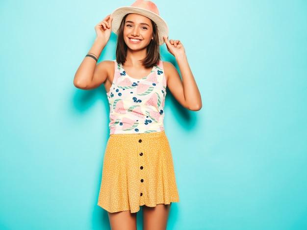 Junge schöne frau, die kamera im hut betrachtet. trendy mädchen im lässigen weißen sommer-t-shirt und im gelben rock in der runden sonnenbrille. positive frau zeigt gesichtsgefühle. lustiges modell lokalisiert auf blau