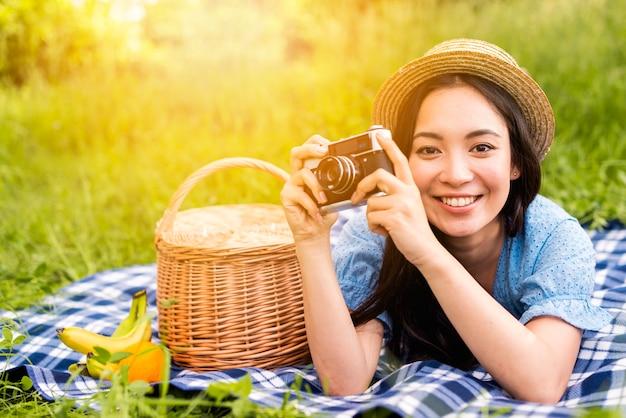 Junge schöne frau, die kamera in der landschaft lächelt und betrachtet