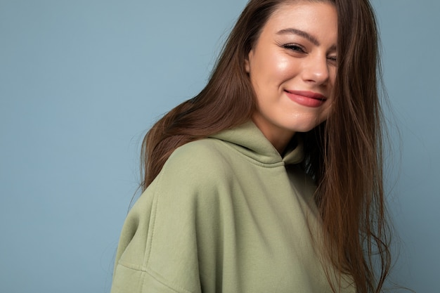 Junge schöne frau, die kamera modisches mädchen in lässiger hipster-kapuzenpullikleidung betrachtet, die positive weiblich ist