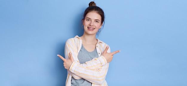 Junge schöne frau, die lässiges weißes hemd trägt, das lokal steht und mit beiden zeigefingern beiseite zeigt.