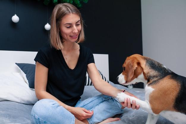 Junge schöne frau, die mit dem hund sitzt auf bett in einem stilvollen schlafzimmer spielt. haustiere zu hause. beagle hund. freundschaft. behaglichkeit