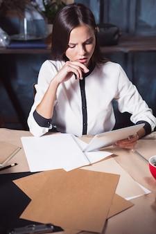 Junge schöne frau, die mit einer tasse kaffee und einem notebook im loft-büro arbeitet