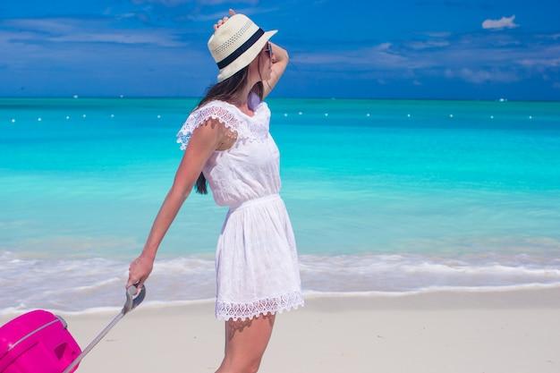 Junge schöne frau, die mit ihrem gepäck auf tropischem strand geht