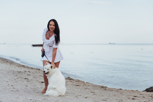 Junge schöne frau, die mit ihrem hund am strand geht