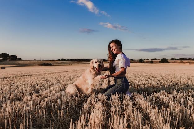 Junge schöne frau, die mit ihrem hund des goldenen apportierhunds auf einem gelben feld am sonnenuntergang geht