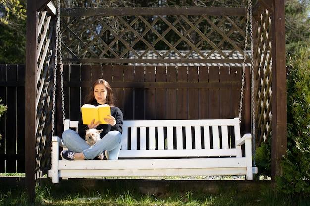 Junge schöne frau, die mit kleinem kühlendem hund des hundes auf hölzerner schaukel in der landschaft sitzt und papierbuch draußen liest