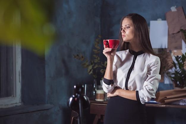 Junge schöne frau, die mit tasse kaffee und notizbuch am dachbodenbüro arbeitet