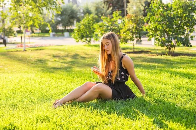 Junge schöne frau, die musik im freien auf kopfhörern genießt, die auf gras liegen und glücklich aussehen