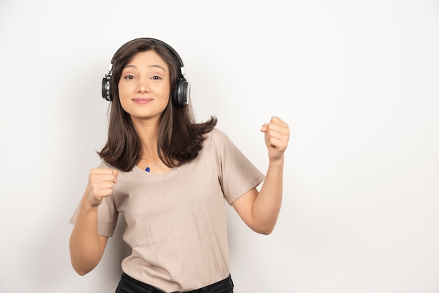 Junge schöne frau, die musik mit kopfhörern hört.
