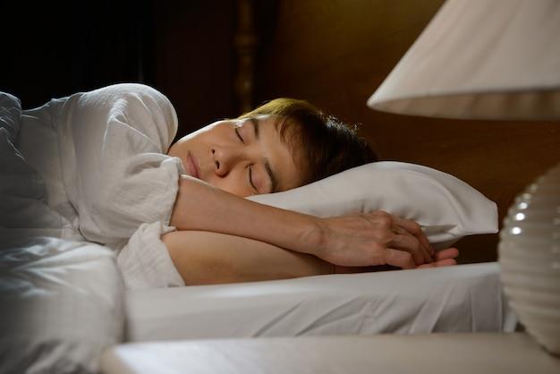 Junge schöne frau, die nachts in ihrem bett schläft