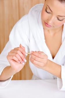 Junge schöne frau, die nagelhaut von den fingern unter verwendung des kosmetikstifts entfernt