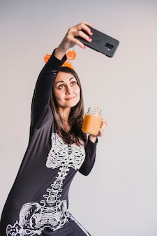 Junge schöne frau, die orangensaft trinkt und ein selfie mit handy nimmt. tragen eines schwarz-weißen skelettkostüms. halloween-konzept. drinnen